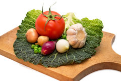 Garlic, onions, peas, tomatoes and cabbage leaf on a kitchen board Stock Photo