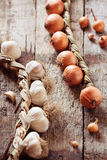 Garlic and onions braids on a wooden background Stock Photography