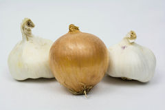 Garlic and onions. Two bulb of garlic with an onion in the middle Stock Photography