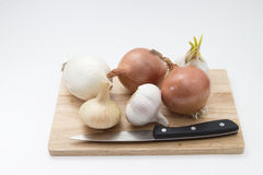 Garlic and onions on a wooden board with knife Stock Photography