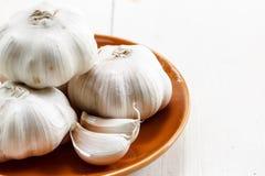 Garlic. Organic Garlic in brown plate Stock Photos