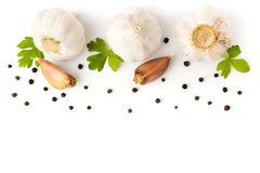 Garlic with parsley leaves and black pepper closeup. On white background, isolated. The view from the top stock images