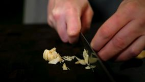 Garlic peeling by hand and knife royalty free stock image