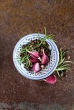 Garlic with pepper and rosemary. Top view of a bowl with aromatic black pepper, fresh rosemary and some garlic royalty free stock photo