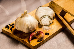 Garlic, pepper and salt. On wooden board and clamp Stock Photography