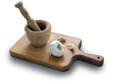 Garlic and Pestle. Garlic and mortar on a wooden board  on white background Stock Photos