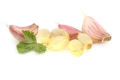 Garlic pills. Isolated on white stock image