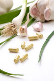 Garlic pills. Closeup of garlic extract pills and fresh garlic leaves and cloves best suited for health, anti-cholesterol and alternative medicine ads royalty free stock photo