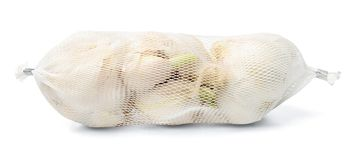 Garlic in plastic net packaging on a white isolated background. royalty free stock photography