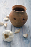 Garlic and Pot. Garlic next to a clay pot for conservation Royalty Free Stock Photo