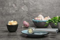 Garlic press with crushed clove on table. Kitchen utensil stock photography