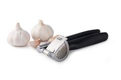 Garlic press and garlic Stock Images