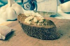 Garlic press on a piece of bread Royalty Free Stock Photos