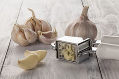 Garlic press on wooden background Royalty Free Stock Photography