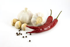 Garlic, red and black pepper. Are isolated on a white background Royalty Free Stock Photo