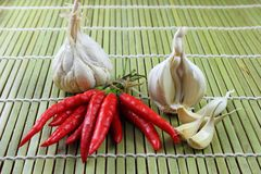 Garlic and red chili on bamboo Royalty Free Stock Photography