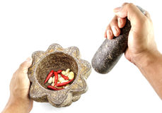 Garlic and red chili pepper in stone mortar with hand holding Royalty Free Stock Photo