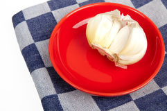 Garlic on red stone plate. Part of a garlic bulb on a red stone plate and a dishcloth beneath it Stock Photography