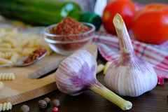Garlic, red tomatoes, dry Georgian spices for gourmets, olive oil, pasta on a wooden table. The concept of cooking, natural royalty free stock photos