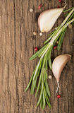 Garlic and rosemary on a wooden background Stock Images