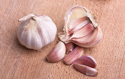 Garlic on rough chopping board Royalty Free Stock Photography