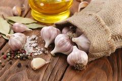Garlic in a sack, sea salt, pepper, bay leaf, sunflower oil Stock Photos