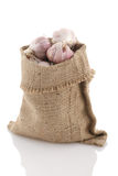 Garlic in a sack on a white background Royalty Free Stock Photos