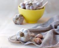 Garlic on sackcloth napkin. With yellow ceramic bowl full of garlic on the background Royalty Free Stock Image