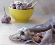 Garlic on sackcloth napkin. With yellow ceramic bowl full of garlic on the background Stock Photo