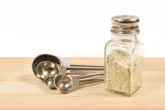 Garlic salt shaker and spoons Stock Images