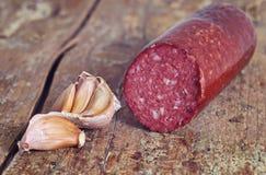 Garlic and sausage. Raw garlic and sausage  on the table Stock Photos