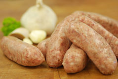 Garlic Sausges. Pork sausages with garlic on butcher's block with fresh garlic and parsley Stock Photography