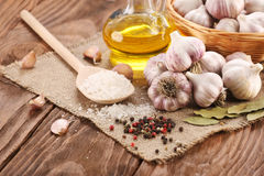 Garlic, sea salt, pepper, sunflower oil, bay leaf, against a bac Royalty Free Stock Photo