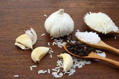 Garlic sea salt  rice grains and black pepper on grunge chopping Royalty Free Stock Images