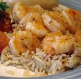 Garlic Shrimp. Closeup of a plate of garlic shrimp on a bed of rice royalty free stock photo