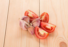 Garlic and sliced tomatoes on wood table. Royalty Free Stock Images