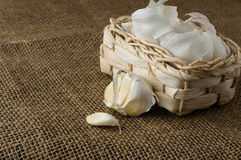 Garlic in a small basket. On jute table cloth close up, space for text royalty free stock photo