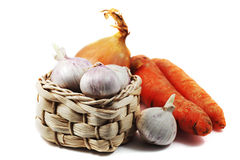 Garlic in a small wicker basket, carrots and onions Stock Photos