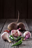 Garlic, spicy green pepper and beetroot on wooden table. Garlic, spicy green pepper and beetroot on a wooden table. Spices, condiments, vegetables. The concept Royalty Free Stock Photography