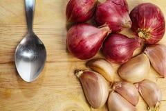 Garlic and spoon on Chopping Block Stock Photo