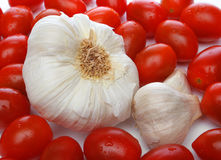 Garlic surrounded by cherry tomatoes Royalty Free Stock Photos