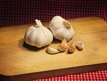 Garlic on a table with a red tablecloth Royalty Free Stock Photography