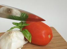 Garlic Tomato and Basil. Sharp knife cutting garlic clove, roma tomato and fresh basil where image is reflected in the knife Royalty Free Stock Photography