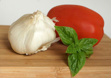 Garlic, Tomato, and Basil. Fresh garlic, tomato and basil on wood cutting board Royalty Free Stock Images