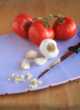 Garlic and Tomatoes on cutting board vertical Royalty Free Stock Photo