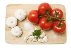Garlic and tomatoes on wooden board Stock Photo