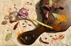 Garlic and various spices for dressing dinner dishes on a wooden board. Dark wood, bay leaf, chili pepper, nutmeg. Top. Close up view flat lay food vegan photo stock photography