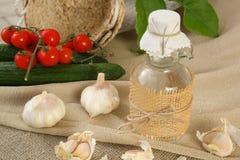 Garlic vinegar. A glass bottle of garlic vinegar. Fresh garlic in the background royalty free stock image