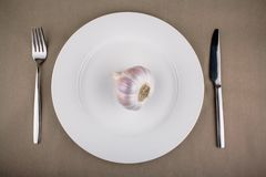 Garlic on white plate with fork and knife Stock Photography