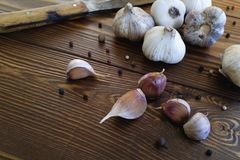 Garlic whole and sliced and spicy spices on a wooden table. Gourmet seasoning. Natural flavor. Antibacterial, boosts immunity. Traditional medicine against stock image